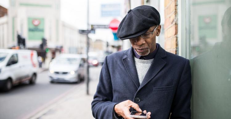 black elderly man outside on phone hat