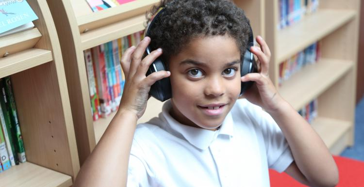 young boy with headphones listening to audiobook