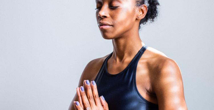 women in yoga pose black sports bra prayer hands