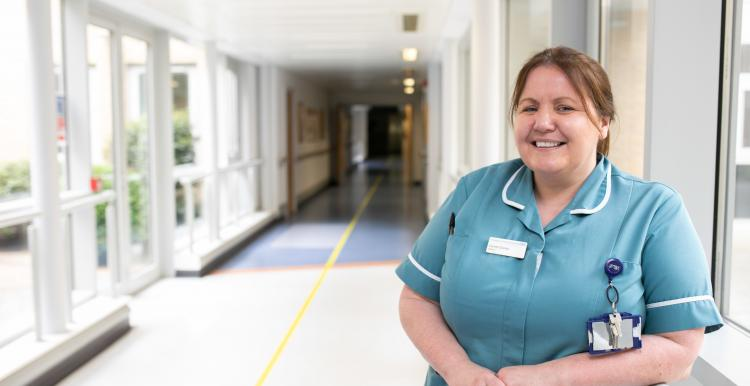 Nurse standing in hospital corridor in scrubs