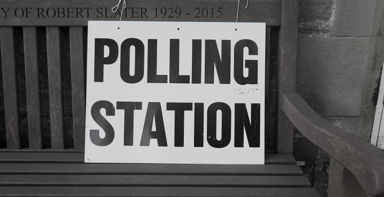 Polling station sign on bench