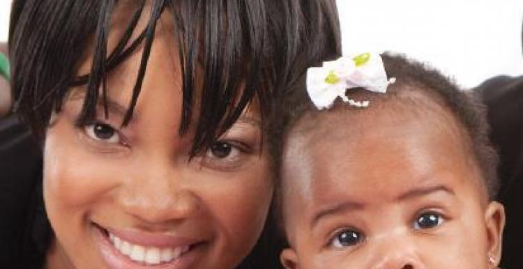 Close up of woman and her baby smiling at the camera