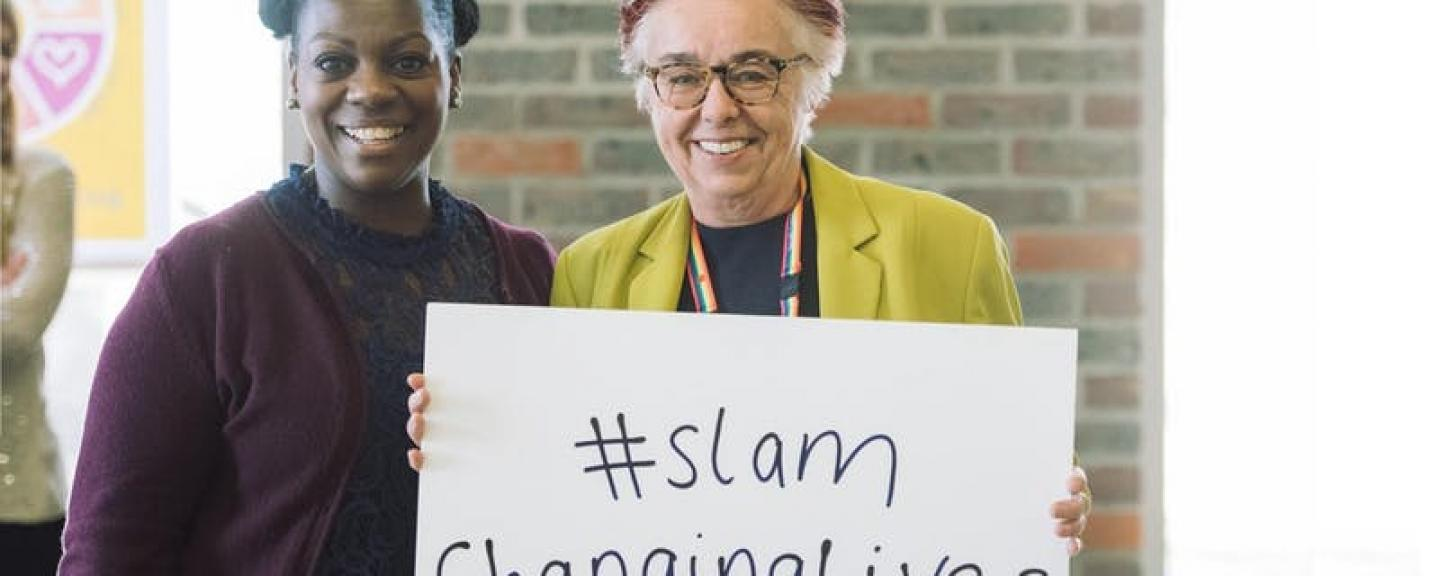 Two women smiling holding a 'SLAM Changing lives' poster