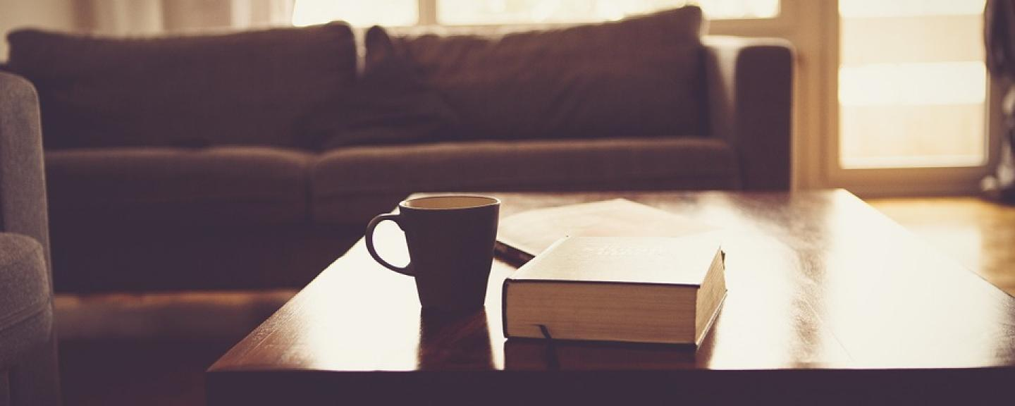 cup and book on top of coffee table