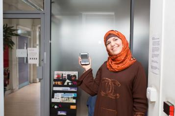 woman with headscarf holding phone in hospital