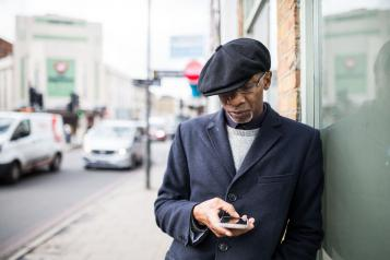 black elderly man outside on phone hat