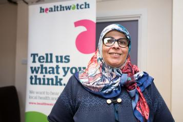 woman wearing headscarf standing in hospital healthwatch sign
