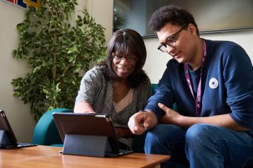 two people around a tablet device