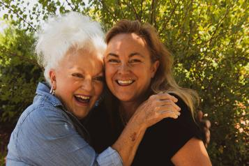 older women hugging and laughing