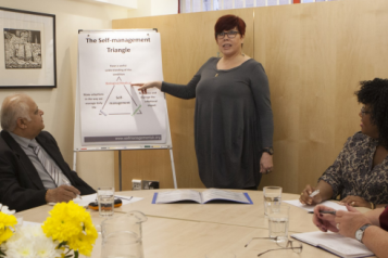Group of people in a training session, with lady pointing to a flipchart.