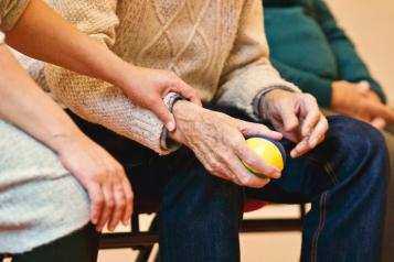 occupational therapy man squeezing ball with nurse