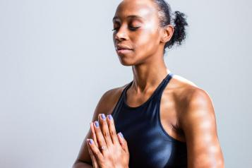 women in yoga pose black sports bra prayer hands