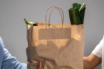 Hands holding out brown paper bag full of food