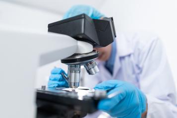 Person leaning over a microscope in a scientific laboratory
