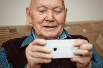 Image of older man holding iphone