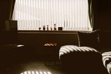 sofa besides window in dimly lit flat