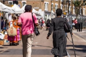 The back of two ladies walking in east street market