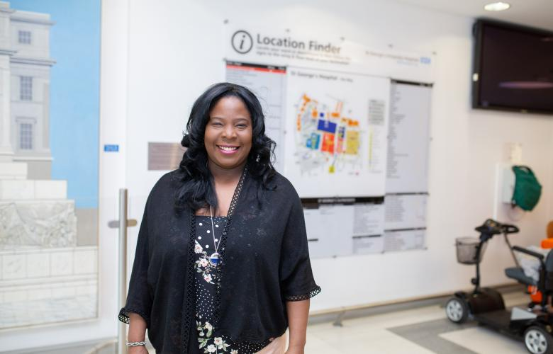 Woman in hospital standing in front of map sign