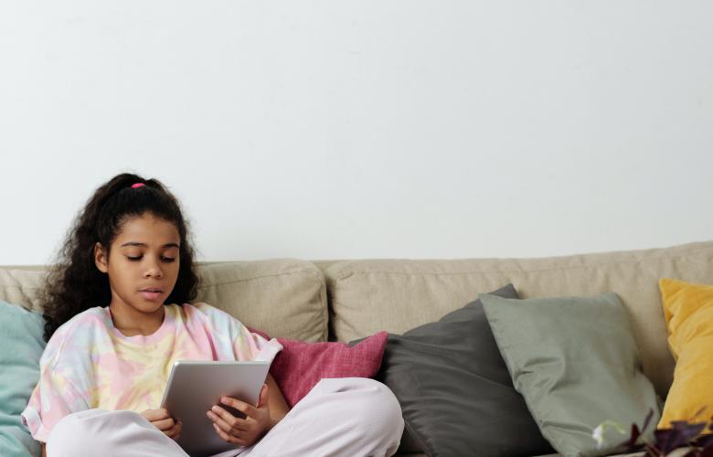 girl sitting on sofa using tablet