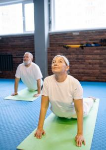 An older man and woman doing yoga together on colourful mats
