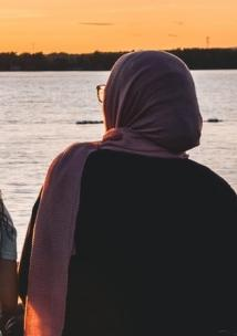 back of a lady in a hijab looking at the sunset